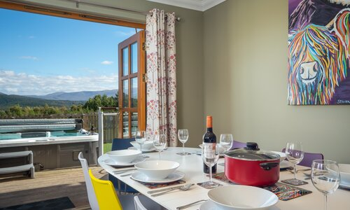 Snowmass Lodge, Aviemore - Dining room with doors opening out to the enclosed garden and hot tub.