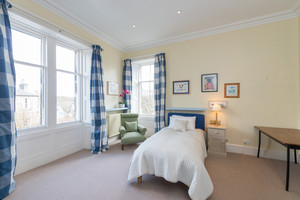 Single bed, blue chequed curtains, green chair ...