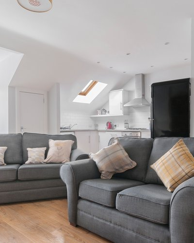 Edinburgh-Flats-self-catering-holiday-apartment-Royal-Mile-High-Street-lounge - Bright spacious Living/Dining/Kitchen open plan area with lovely wooden floors and 2 modern grey sofa and a double sofa bed which sleeps 2 people