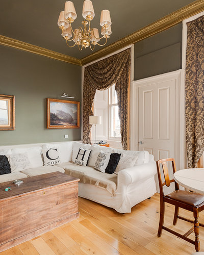 """CastleEsplanade_3 - Comfortable corner sofa with decorative cushions saying """"cosy"""" and """"home"""""""