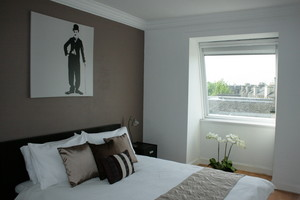 Bedroom with double bed and Charlie Chaplin picture on the wall.