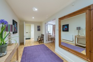 Spacious hallway with purple rug and large wall mirror.
