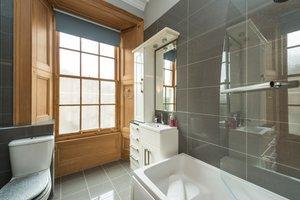 Modern grey tiled bathroom with large window.