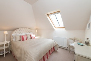 Double bedroom with roof window and sloped ceiling.