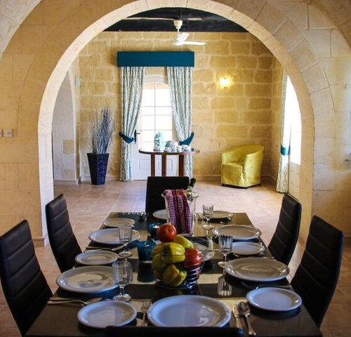 Dining Area in Malta villa - Dining area with table, chairs and plates