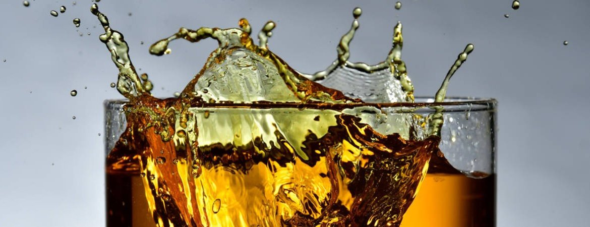 Whisky splashing as ice hits the glass