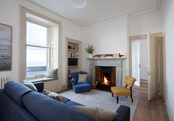 Seaside pet friendly apartment - Living room with open fire and sea views.