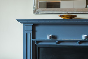 Close up detail of blue fire surround, mirror and candles.