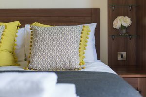 Coates Gardens Apartment Master Bedroom - Close up of bed in Master Bedroom with yellow and patterned cushions.
