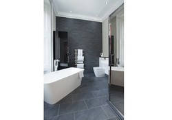 The large bathroom boasts a standalone bathtub as well as a large shower cubicle with a rainfall shower head