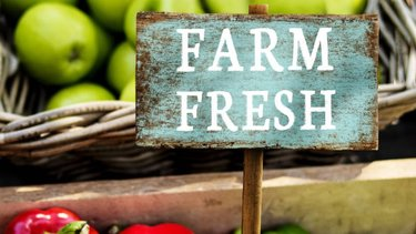 Fruit and vegetables for sale with a sign saying Farm Fresh