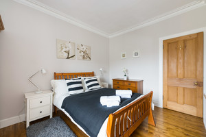 Double bed with black and white bedding, wooden floor and furniture.