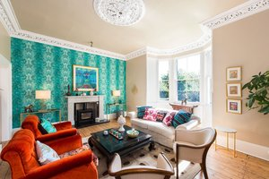Drawing room with bold teal wallpaper, chairs and sofas, wood burning stove, coffee table