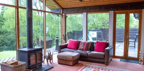 Ptarmigan Lodge - 4 Bed Home with Hot Tub. Living room area with log burning stove