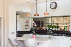 Kitchen with white units, black worktops and breakfast bar