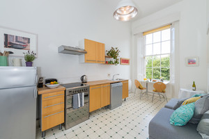 Kitchen with living and dining space, tiled floor, wooden units, lots of natural light.
