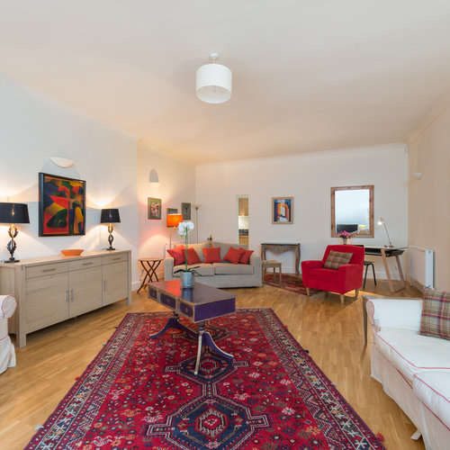 Large lounge with red rug in the centre and artwork on the walls.