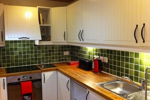 Fully equipped kitchen with green tiles, white units, wooden worktops