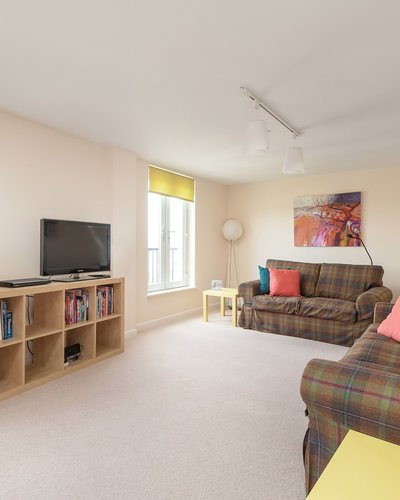 Newhaven Place 2 - Family lounge with tartan sofas and decorative art work