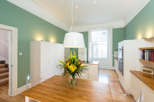 Albany Street Townhouse Dining Kitchen - Large, modern kitchen with green walls and white fittings. Large wooden table with clear chairs.