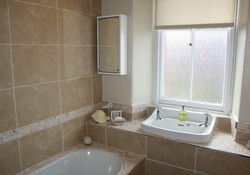 Luxurious bathroom with deep roll top bath and lovely shower over
